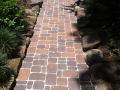 brick stone paver pathway though boulders