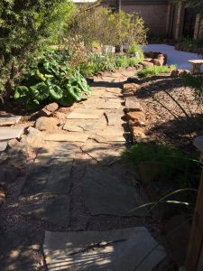 Flagstone pathway  through mulch and bushes in Brownsville, TX